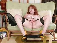 Red haired mature woman is wearing stockings and shoes with high heels and fingering her pussy